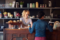 Kund i coffee shop som beställer genom att använda den Digital minnestavlan Arkivfoton