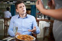 Kund i restaurang som klagar till servitrins About Food Royaltyfri Foto