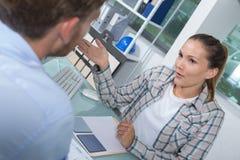 Kund och kvinnligt finansiellt medel i diskussion p? skrivbordet arkivbild