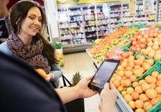 Kund som använder den Digital minnestavlan med kvinnan i livsmedelsbutik royaltyfri bild