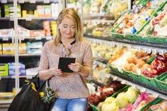Kund som använder den Digital minnestavlan, medan shoppa i livsmedelsbutik royaltyfri bild