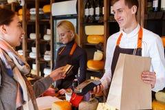 Kund som betalar för beställning av ost i speceriaffär arkivbild