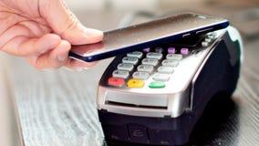 Kund som betalar med NFC-teknologi vid mobiltelefonen på terminalen arkivbilder