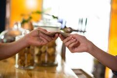 Kund som betalar räkningen vid kassa på räknaren i café Fotografering för Bildbyråer