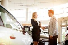 Kund som köper en bil på återförsäljaren royaltyfri bild