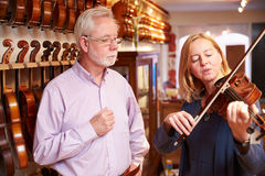 Kund som ut försöker fiolen i Music Store Royaltyfri Bild