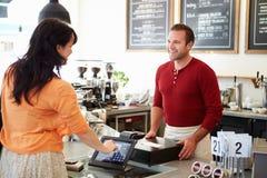 Kunde, der in der Kaffeestube unter Verwendung des mit Berührungseingabe Bildschirms zahlt Stockfotografie