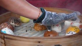 Kunde, der frisch gekochte gedämpfte Brötchen, bao oder Baozi, Schweinefleischmehlklöße Chinesen, Nahrung im Bambusdampfer wählt  stock footage