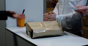 Kunde, der gesch?digtes Paket am Kundendienstschreibtisch empf?ngt stock video