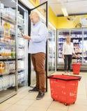 Kunde, der Handy am Kühlschrank im Supermarkt verwendet Stockfoto