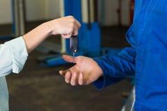 Kunde, der ihr Autoschlüssel zum Mechaniker gibt Lizenzfreie Stockbilder