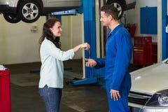 Kunde, der ihr Autoschlüssel zum Mechaniker gibt Stockfoto
