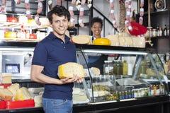 Kunde, der Käse während Verkäuferin Working At Counter hält Stockfotografie