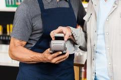 Kunde, der mit Mobiltelefon unter Verwendung NFC zahlt Stockbild