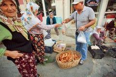 Kunde, der traditionelles Brot Simit auf gedrängtem türkischem Dorfmarkt kauft Stockfotografie