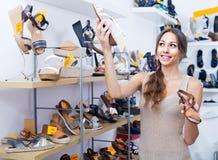 Kunde, der von zwei Schuhen wählt Stockfotografie