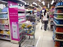 Kunde geht hinter die Mund- und Körperpflegeprodukte auf den Regalen eines Lebensmittelgeschäfts Lizenzfreies Stockbild