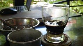 Kunde setzt Eis in Kaffee mit Milch ein, bevor er trinkt Unter Verwendung eines vietnamesischen traditionellen phin Filters im Ca stock video footage