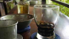 Kunde setzt Eis in schwarzen Kaffee ein, bevor er trinkt Unter Verwendung eines vietnamesischen traditionellen phin Filters im Ca stock footage