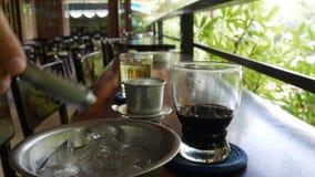 Kunde setzt Eis in schwarzen Kaffee ein, bevor er trinkt Unter Verwendung eines vietnamesischen traditionellen phin Filters im Ca stock video