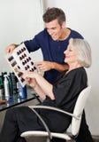 Kunde und Friseur Selecting Hair Color von Lizenzfreie Stockfotos