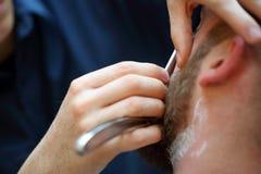 Kunde während des Bartes, der im Friseursalon rasiert Lizenzfreies Stockbild