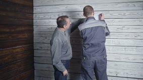 Kunden applicerar med byggmästaren om reparationen av hans rum på bakgrunden av en trävägg Kunden önskar arkivfilmer