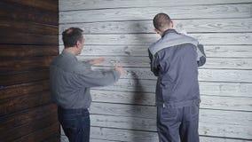 Kunden applicerar med byggmästaren om reparationen av hans rum på bakgrunden av en trävägg Kunden önskar stock video