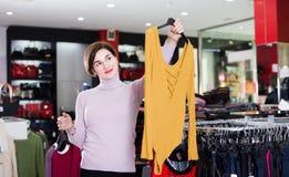 Kunden betraktar alternativ för blusar Royaltyfri Foto