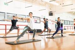 Kunden, die Kriegers-Haltung II an im Fitnessstudio durchführen lizenzfreie stockfotografie