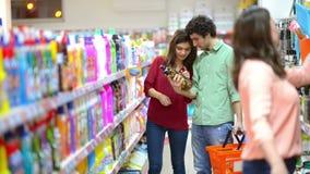 Kunden, die Reinigungsprodukte im Supermarkt wählen stock footage