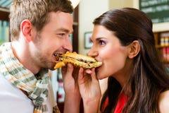 Kunden, die Würstchen im Schnellimbisssnackbar essen Stockfotos