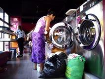 Kunden eines Waschautomaten füllen Waschmaschinen und Trockner mit ihrer Wäscherei lizenzfreies stockbild
