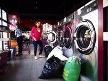 Kunden eines Waschautomaten füllen Waschmaschinen und Trockner mit ihrer Wäscherei stockbild