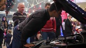 Kunden im Ausstellungsraum besprechen Fahrzeug mit offener Haubennahaufnahme stock video footage