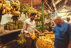 Kunden och banansäljaren köpslår på bondefruktmarknad Arkivfoto