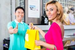 Kunden och shoppar assistenten i modelager Royaltyfri Fotografi