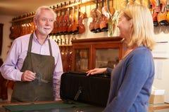 Kunden som lämnar fiolen för reparation shoppar in Arkivbild