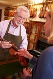 Kunden som lämnar fiolen för reparation shoppar in Royaltyfria Foton