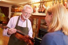 Kunden som lämnar fiolen för reparation shoppar in Fotografering för Bildbyråer