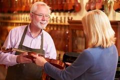 Kunden som lämnar fiolen för reparation shoppar in Arkivbilder