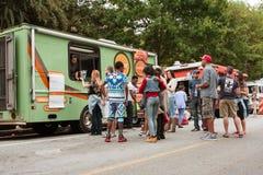 Kunden-Stand in der Linie, zum von Mahlzeiten von den Lebensmittel-LKWs zu kaufen stockbild