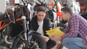 Kunden talar med konsulenten om mopeden stock video