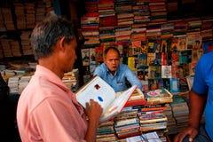 Kunden- und Buchhändler auf dem asiatischen Straßenmarkt Stockbilder