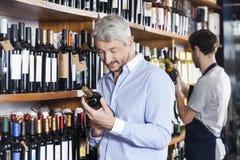 Kunden-und Verkäufer-Looking At Wine-Flaschen Stockfotos