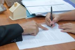 kunden undertecknar bostadslånavtalet med fastighetsmäklaren royaltyfri bild