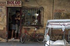 Kunden warten an einer alten SchmuckReparaturwerkstatt, mit einem tuk-tuk vor dem Geschäft in Tabaco, die Philippinen lizenzfreie stockfotografie