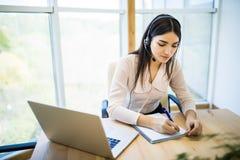 Kundenbetreuungsbetreiber, der in einem Call-Center-Büro mit Laptop arbeitet Stockbild