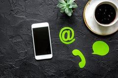 Kundenbetreuungsdesktop mit E-Mail-Zeichen und Mobile auf dunklem Draufsichtmodell des Hintergrundes Stockbild