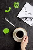 Kundenbetreuungsdesktop mit Kontakt wir Zeichen und Kaffee auf Draufsicht des dunklen Hintergrundes Stockfoto